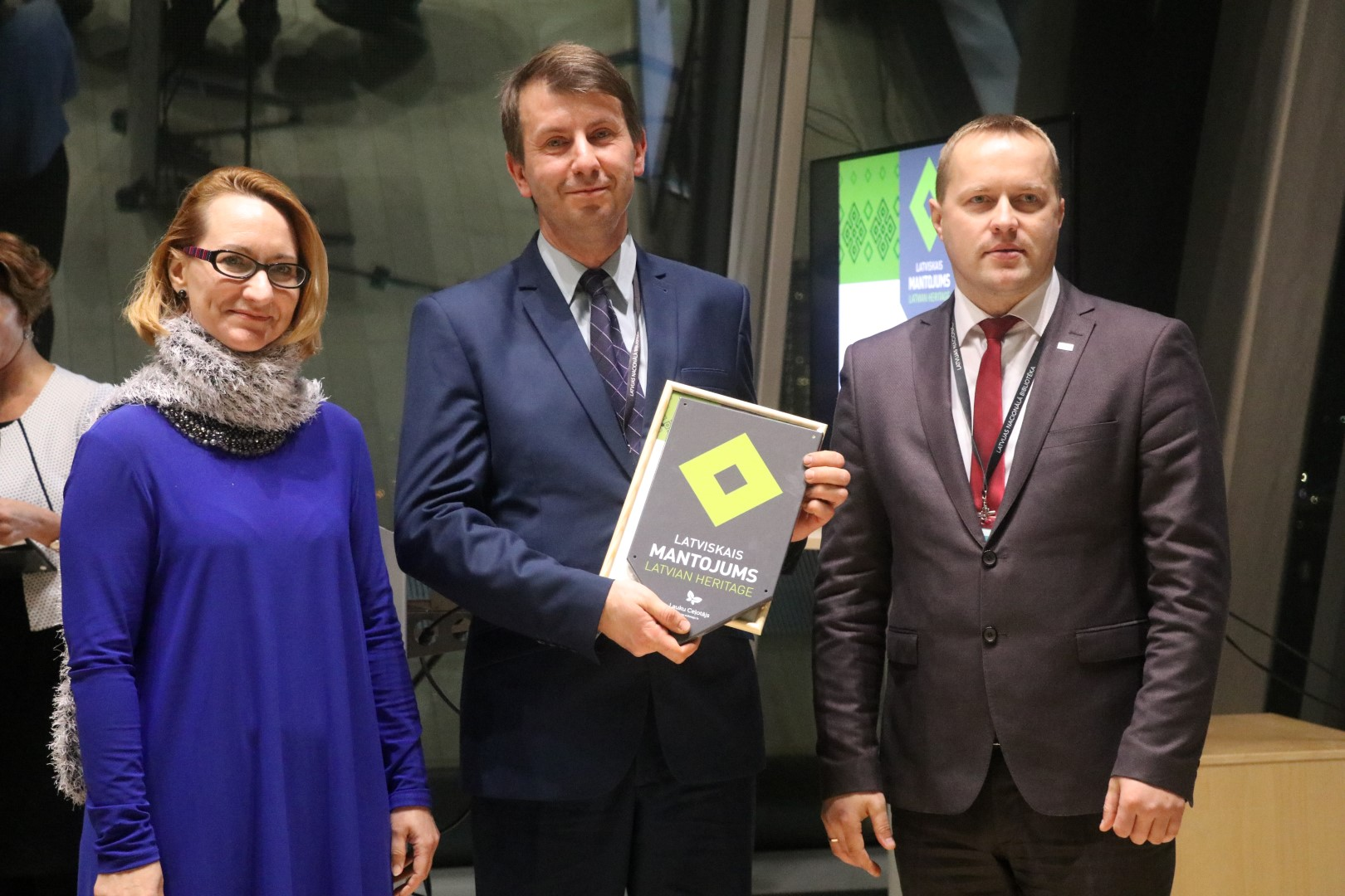 Uģis Puzulis (attēlā vidū) ar saņemto kultūras zīmi un apliecinājuma rakstu, Latvijas Republikas kultūras ministre Dace Melbārde, LPS priekšsēža vietnieks Gints Kukainis